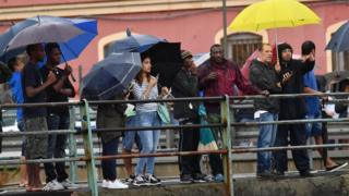 Crowd of people with umbrellas look on at the collapsed bridge