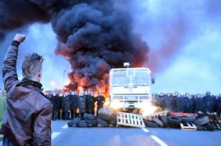 A protester holds up his fist as riot police prepare to intervene to disperse refinery worker holding a blockade of the oil depot of Douchy-Les-Mines