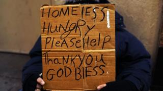 A homeless person holds up a sign