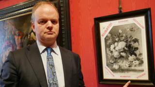 Uffizi gallery head Eike Schmidt with a photo of the stolen painting, Vase of Flowers