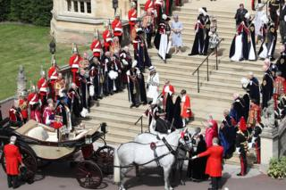 Guards, military, other members of the Royal Family and the Knights of the Garter look on as Queen Elizabeth II walks down the steps to her carriage during the Order of the Garter Service at Windsor Castle