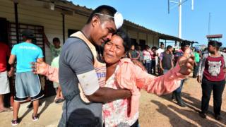 A survivor of a capsized boat is embraced by a relative in Puerto Lempira, Honduras, 4 July 2019