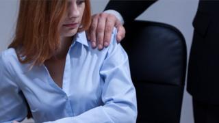Man touches woman's shoulder
