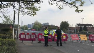 Officers next to a police cordon