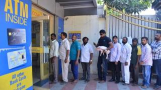 Ravi Babu with the piglet standing in line at the ATM
