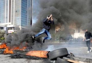 in_pictures A protestor jumps over a burning barricade during a protest over economic hardship and lack of new government in Beirut