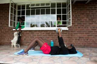 A boy exercises on the ground as his siblings watch from a window