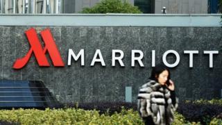 a woman walking past Marriott signs in Hangzhou in China's Zhejiang province.