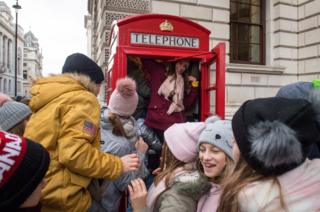 in_pictures Polish tourists trying to see how many of them can fit into a red telephone box, in Westminster, London