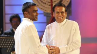 Sri Lankan president Maithripala Sirisena holds the hands of a former Tamil Tiger insurgent Sivaraja Jenivan after setting him free during a function to mark the first anniversary of his election to the prime minister's office in Colombo