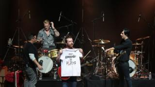 イーグルス・オブ・デス・メタルがパリ・オランピア劇場で演奏。ジェシー・ヒューズ(中央)が「本当にパリにいきたい」と書かれたTシャツを広げて見せた(16日)