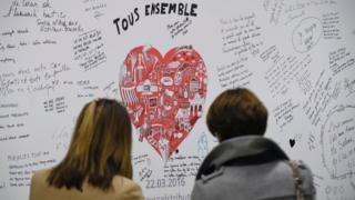 People read messages on a commemorative wall at the Maelbeek - Maelbeek metro station in Brussels (25 April 2016)