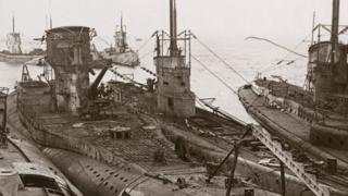 A stereo card image of German submarines moored at Harwich at the end of World War I, November 1918. The vessels were surrendered to Britain under the terms of the armistice signed by Germany.