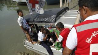 Members of the Myanmar Red Cross society move a wounded child from a boat to an ambulance that will transport him to Sittwe Hospital, in Sittwe, Rakhine State, western Myanmar, 24 March 2020