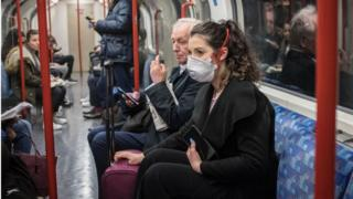 A woman wears a face mask on the London Underground