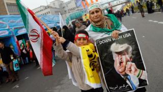 An Iranian woman holds a placard showing a caricature of US President Donald Trump being punched by a hand wearing a bracelet of the Iranian flag