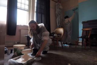 People painting walls with roller brushes
