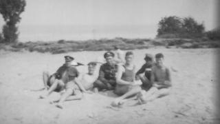Soldiers sitting on a beach in 1919