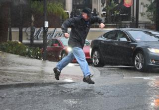Man jumps over, or into, a large puddle in Glendale