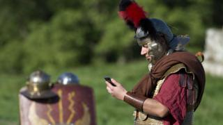Man dressed as Roman soldier looks at mobile phone