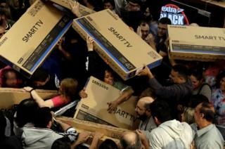 Shoppers reach out for television sets as they compete to purchase retail items on Black Friday.