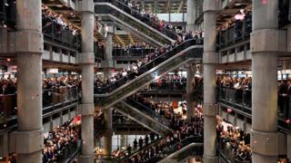 """Workers stand for a poppy drop during a Remembrance Service at the Lloyd""""s building in the City of London"""