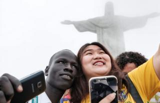 """South Sudan""""s athlete Yiech Pur Biel (L) for the Refugee Olympic Team (ROT) takes pictures with a tourist in front of the statue of Christ the Redeemer ahead of Rio 2016 Olympic games in Rio de Janeiro, Brazil, on July 30, 2016"""