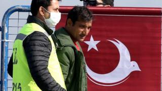 トルコのディキリ港で警察に誘導される移民(3日)