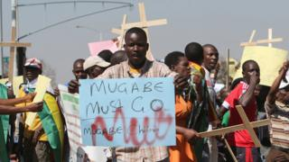 "Protesters in Harare, Zimbabwe, one holding a ""Mugabe must go"" sign and others holding wooden crosses - Wednesday 3 August 2016"