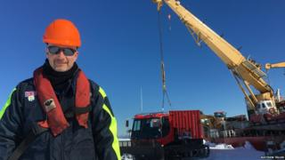 Peter Gibbs in foreground dressed in warm winter clothes. Standing on white snow and bright blue sky behind. Large ship and crane in background.