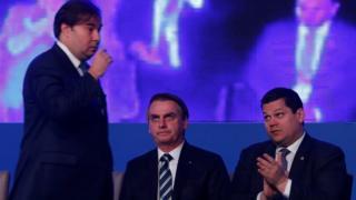Rodrigo Maia passa por Jair Bolsonaro e Davi Alcolumbre durante cerimônia em Brasília em 9 de abril