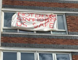 """Banner hanging out of tower block window saying: """"Not enough staff to keep us safe."""""""