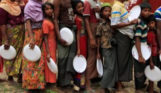 Rohingya refugees line up with plates.