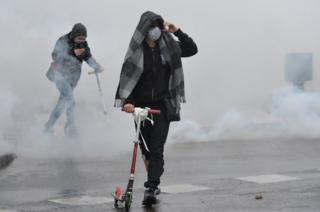 A protester stands among smoke during clashes with police in Nantes, western France