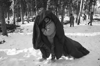 A soldier walks with a parachute to the thermal shelter he is building