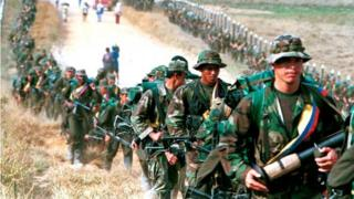 Leftist rebels of the Revolutionary Armed Forces of Colombia (FARC) patrol by a roadway near to San Vicente de Caguan, Caqueta province, Colombia, January 9. 1999
