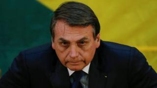 Bolsonaro aparece com feição séria, com cores verde e amarela no pano de fundo