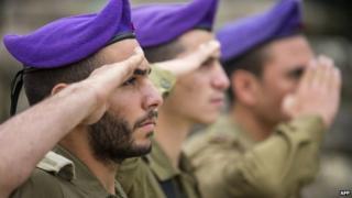 A bearded Israeli soldier saluting alongside a clean-shaven colleague
