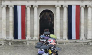 Visitors, many of them carrying umbrellas, stand close to the entrance of Les Invalides in Paris on 29 September 2019.