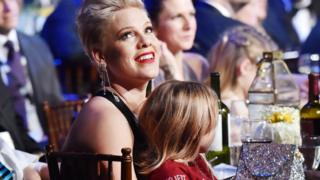 Pink sits in a chair with her daughter sat on her lap