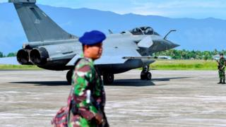 Indonesian soldiers stand guard near a French Rafale fighter jet at an air force base in Blang Bintang, Aceh province, on 19 May