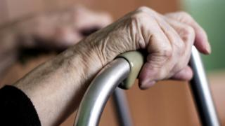 Elderly person holding a walking frame