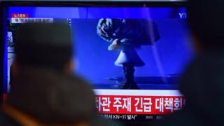 People watch a news report on North Korea's first hydrogen bomb test at a railroad station in Seoul on 6 January 2016