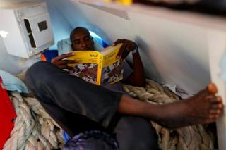 Mohamed, 23, from Sudan, reads a book on board NGO Proactiva Open Arms rescue boat