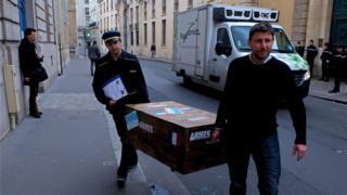 Des militants de l'association Survie déposent une caisse vide devant un bâtiment du ministère de la Défense à Paris.