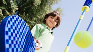 Boy playing swingball