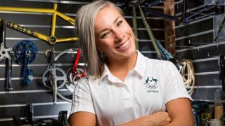 Caroline Buchanan wearing an Australian sports uniform in front of cycling gear