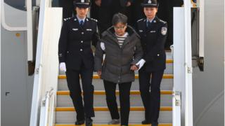 Yang Xiuzhu is escorted down a plane upon arriving at the Beijing Capital International Airport in Beijing (Nov. 16, 2016)