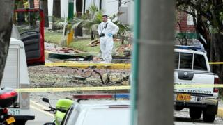 Members of the Colombian Technical Investigation Team (CTI) work at the place where a bomb car caused an explosion