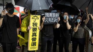 香港市民拿著標語,到法院大樓外聲援被控「暴動」的人。